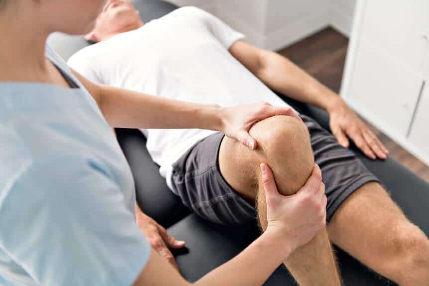 Doctor Treating A Serious Sports Injury Of The Knee