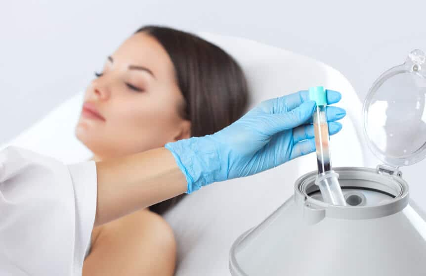 Blood Tube Being Removed From Medical Centrifuge While Woman Waits For PRP Injection